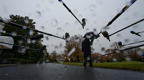 U.S. President Donald Trump walks off under an umbrella after speaking to reporters from the White House in Washington, U.S. December 2, 2019.