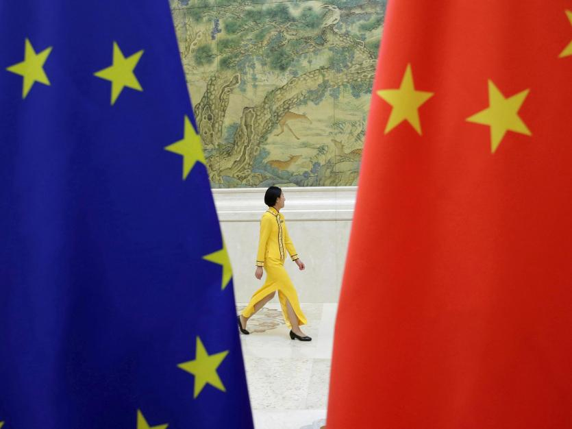 An attendant walks past EU and China flags ahead of the EU-China High-level Economic Dialogue in Beijing, China June 25, 2018.