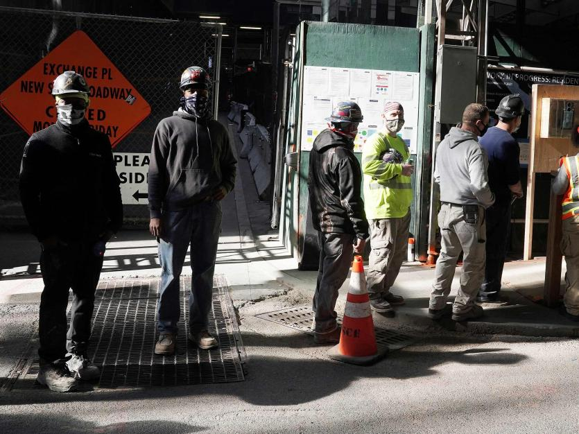 Construction workers wait in line to do a temperature test to return to the job site after lunch, amid the coronavirus disease (COVID-19) outbreak, in the Manhattan borough of New York City, New York, U.S., November 10, 2020.