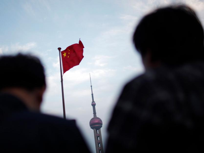 People stand near a Chinese flag as the Oriental Pearl TV tower is seen in the financial area of Pudong in Shanghai, November 1, 2011. China raised its threshold for value-added and business taxes on Monday as part of a wider campaign to help smaller comp