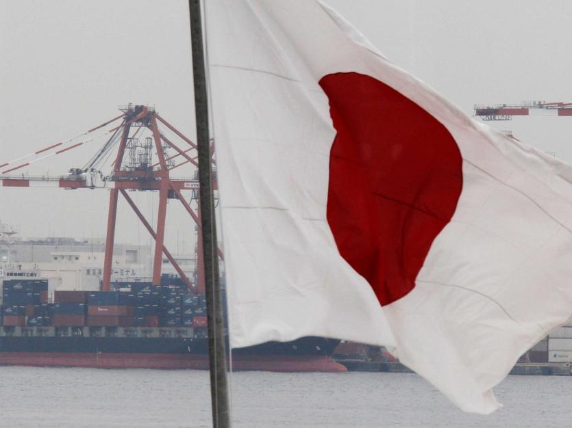 A cargo ship is seen behind Japan's national flag at an industrial port in Tokyo March 8, 2012. REUTERS/Kim Kyung-Hoon