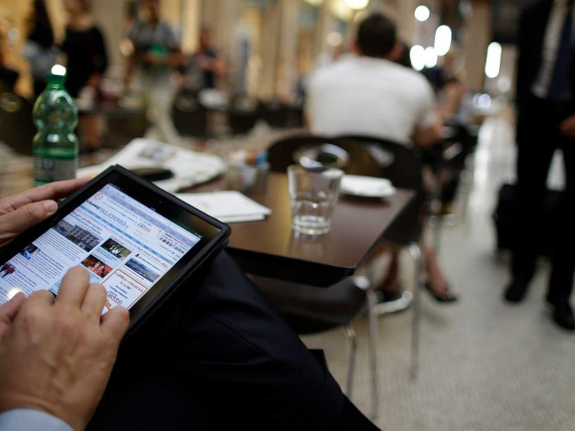 A man poses with his iPad tablet as he sits in a bar, in this photo illustration taken in Rome.