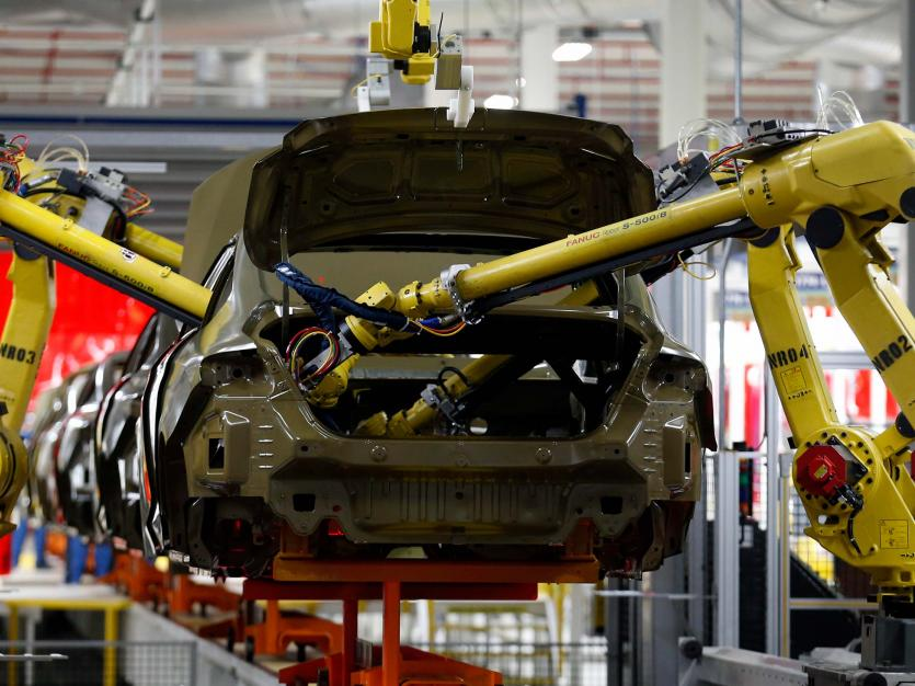 Robotic arms apply sealant to the interior of the frame of a 2015 Chrysler 200 vehicle at the Sterling Heights Assembly Plant in Sterling Heights, Michigan March 14, 2014.