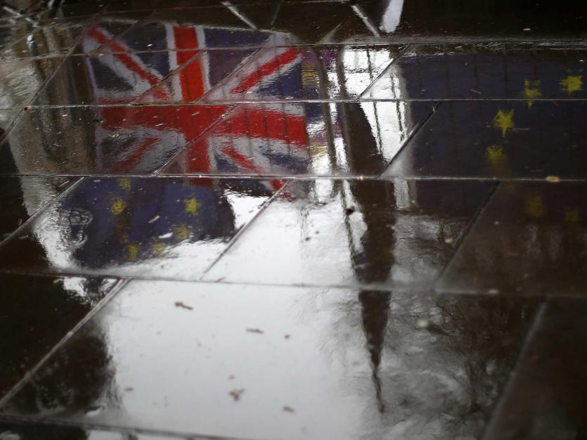 British and EU flags are reflected on the wet pavement in London, Britain, April 2, 2019.