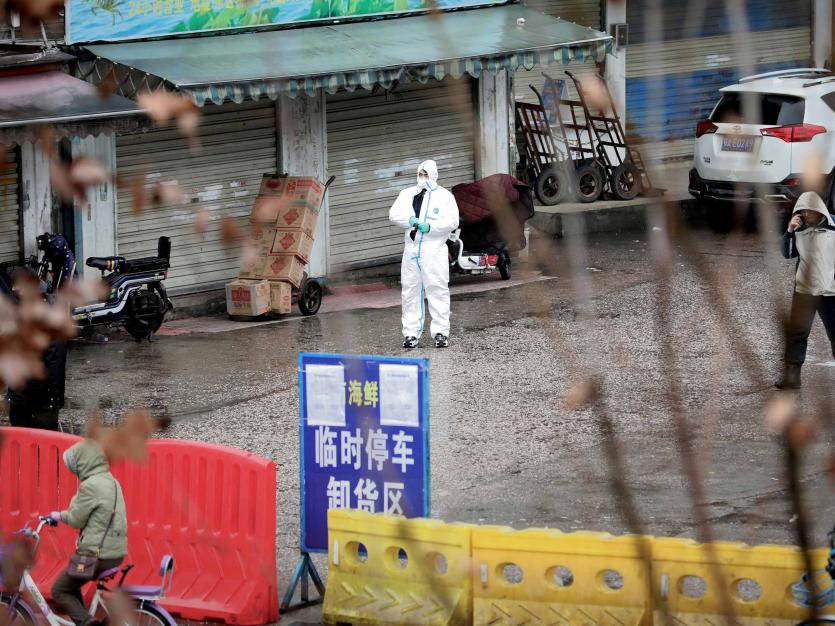 A worker in a protective suit is seen at the closed seafood market in Wuhan, Hubei province, China January 10, 2020. REUTERS/Stringer/File Photo CHINA OUT