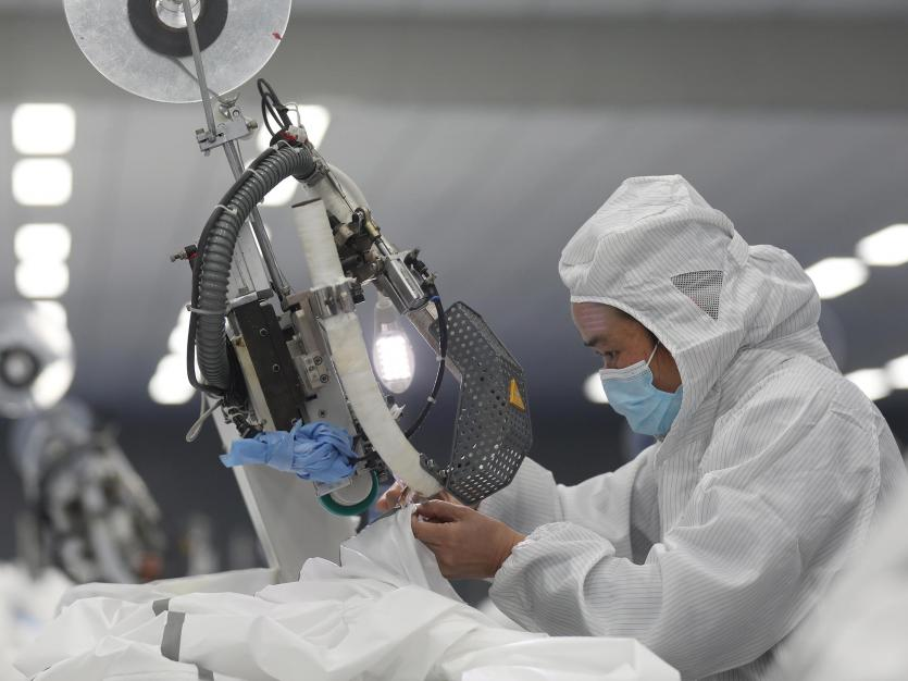 An employee works on a production line manufacturing protective suits at a medical supply factory in Xinzhou district of Wuhan, the epicentre of the novel coronavirus outbreak, in Hubei province, China February 12, 2020.