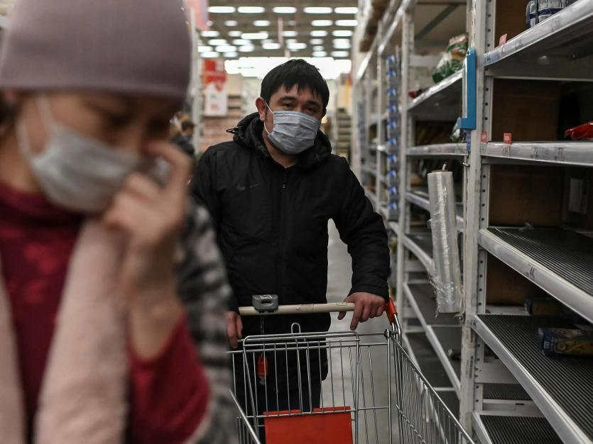 People, wearing protective face masks, walk past partly empty shelves in a store following fear of the outbreak of coronavirus disease (COVID-19). March 17, 2020.
