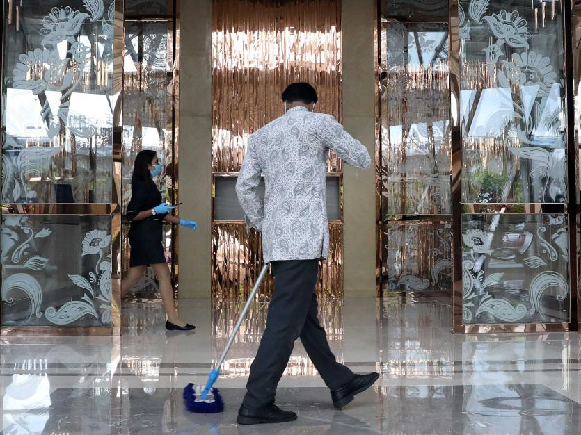 A worker cleans the floor at the entrance of JW Marriott hotel, after authorities eased lockdown restrictions that were imposed to slow the spread of the coronavirus disease (COVID-19), in Kolkata, India, July 15, 2020.