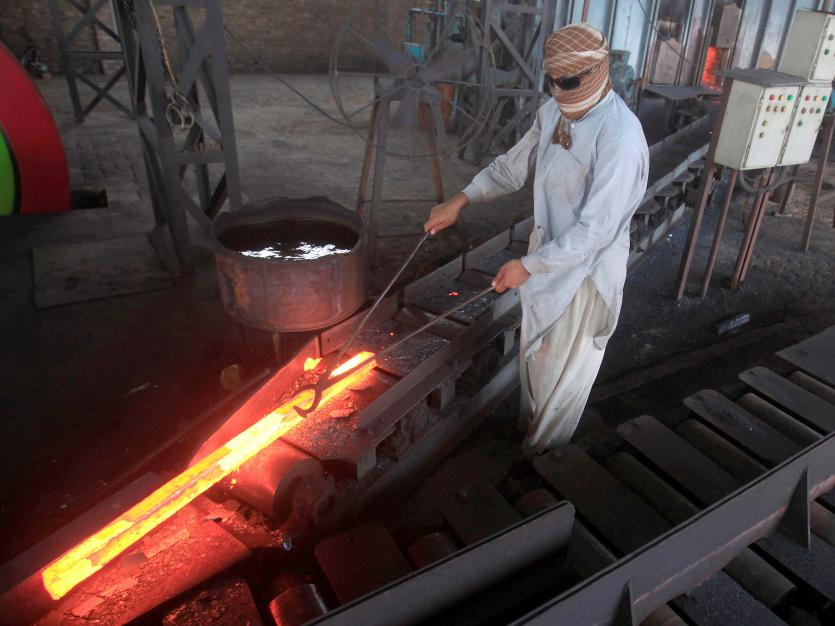 A worker moves heated steel from the furnace in a steel plant in the suburbs of Peshawar, Pakistan.