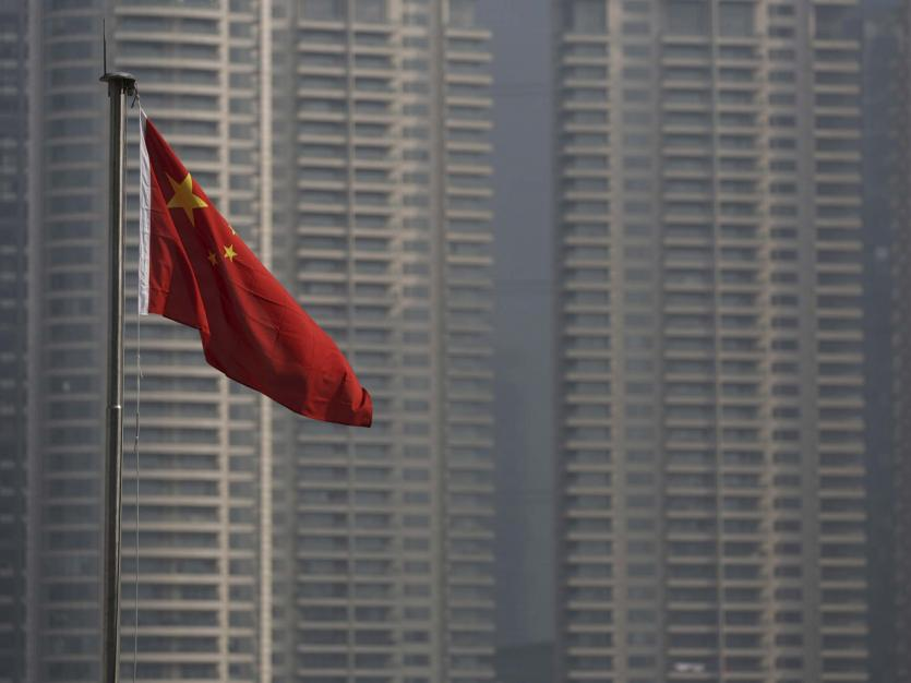 A Chinese flag is seen in front of the financial district of Pudong in Shanghai, China, January 19, 2016.