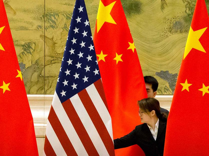 Chinese staffers adjust U.S. and Chinese flags before the opening session of trade negotiations between U.S. and Chinese trade representatives at the Diaoyutai State Guesthouse in Beijing, Thursday, Feb. 14, 2019.