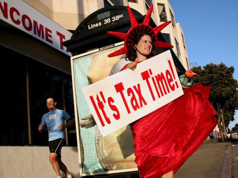 Denise Jameson wears a costume while carrying a sign to remind people passing on foot and in cars that it is income tax filing season in San Francisco, California February 3, 2009.