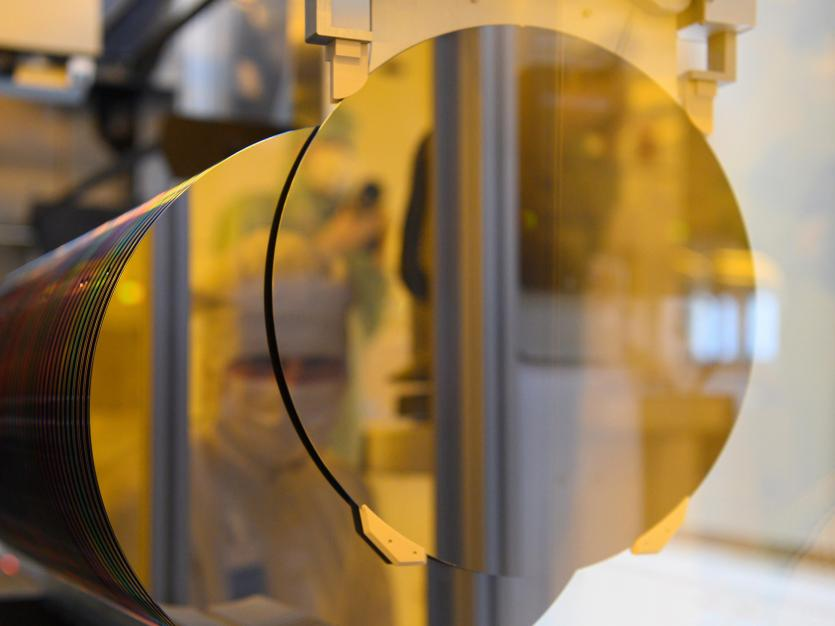 An associate is reflected in a 300-millimeter wafer in the clean room at a semiconductor factory. Picture taken on June 71, 2021.