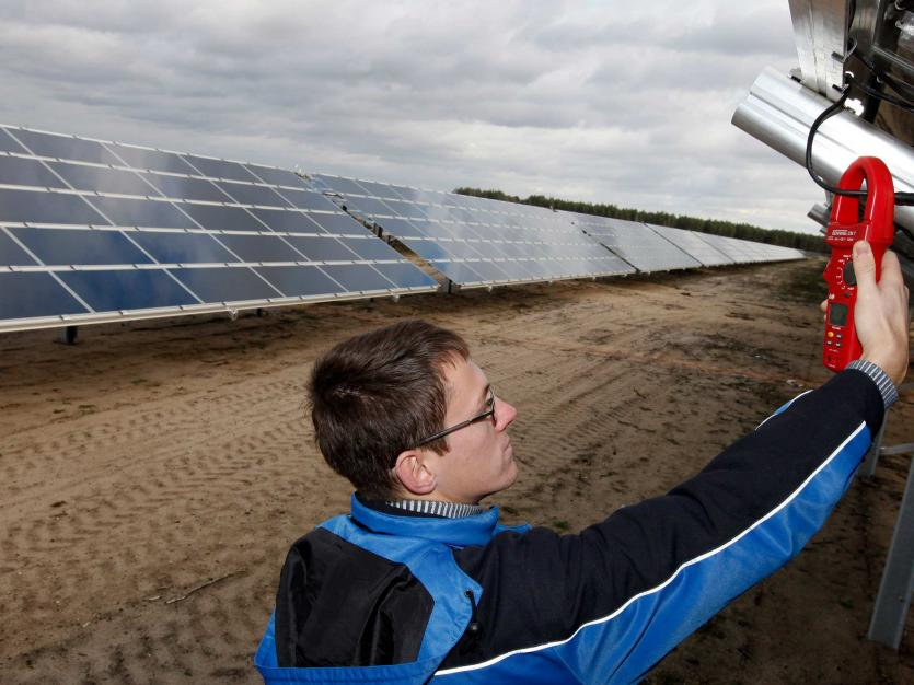 A technician checks the voltage at a solar panel of the Lieberose solar farm in Turnow-Preilack, about 150 km (93 miles) southeast of Berlin.