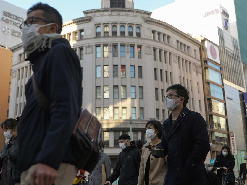 People walk with masks in Tokyo, Japan. March 6, 2020.