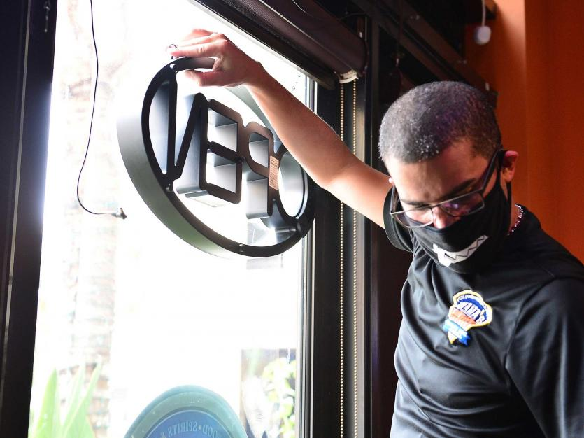 Juana's Latin Sports Bar & Grill employee hangs the open sign in Miramar, Florida.