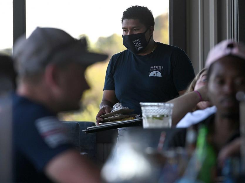 A server is seen wearing a mask as he makes his way around tables where people are seated indoors at the Hudson Taco restaurant, in Newburgh, NY, September 5.