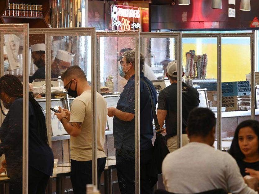 Customers stand at the ordering counter separated by plastic screens as diners eat inside Katz Delicatessen on Manhattan's Lower East Side as indoor dining, New York, NY