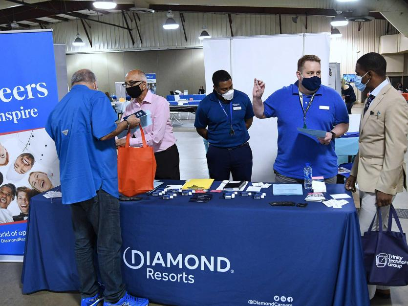 People seeking employment speak to recruiters at the 25th annual Central Florida Employment Council Job Fair at the Central Florida Fairgrounds.