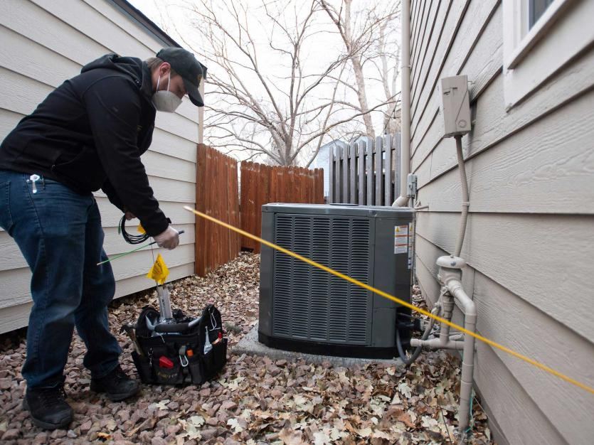 Marcus Baker, a technician, prepares to push a length of fiber optic cable into a residence as he installs broadband service for a customer in Colorado on Thursday, Jan. 21, 2021.