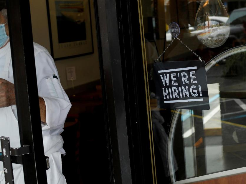 "A ""We're Hiring"" sign advertising jobs is seen at the entrance of a restaurant in Miami, Florida."