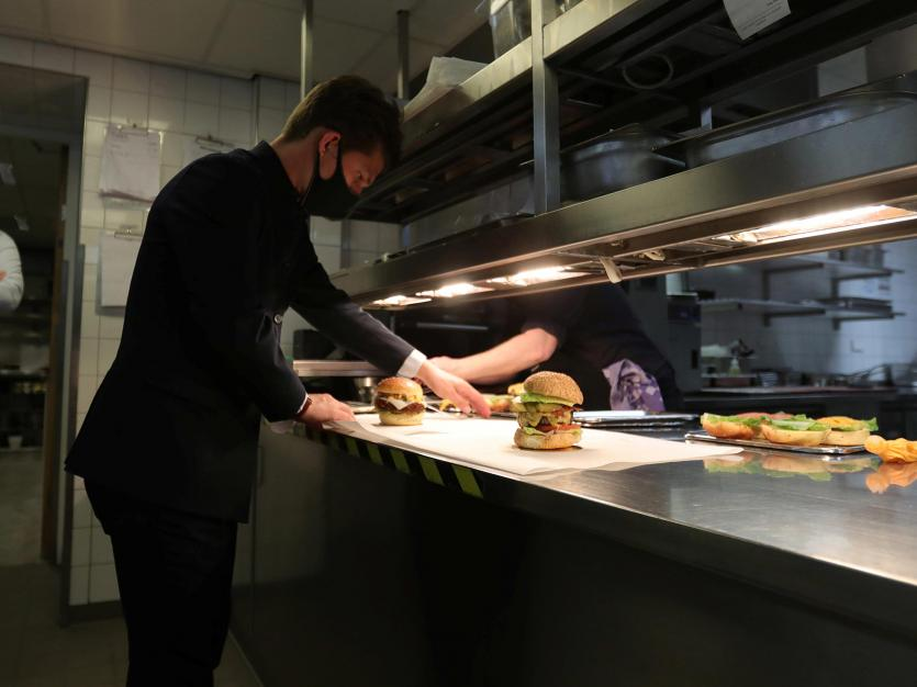 Cooks prepare a burger in the kitchen of a major hotel in Amsterdam, Netherlands, April 14, 2021