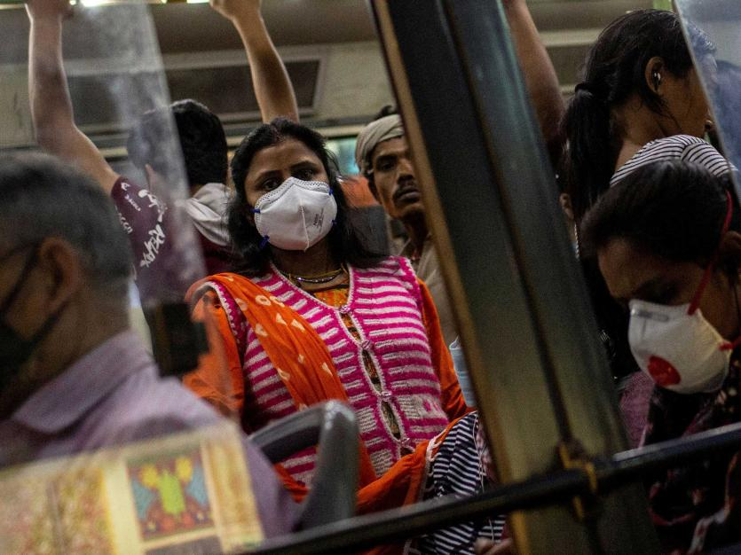 Commuters wearing protective masks as a precaution against the spread of coronavirus disease (COVID-19), travel in a crowded bus during evening rush hour, in New Delhi, India, March 18, 2020.