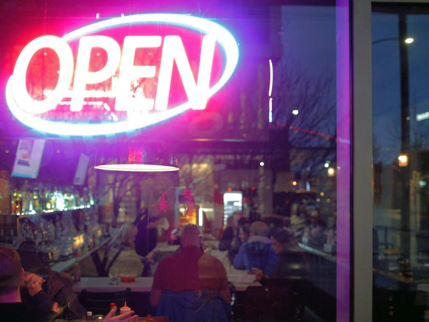 "An ""Open"" neon sign is lit at Pizza Mart in Seattle, Washington, U.S., March 13, 2020."