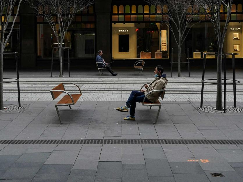 People sit in the quiet city centre in Sydney, Australia, August 23, 2021.