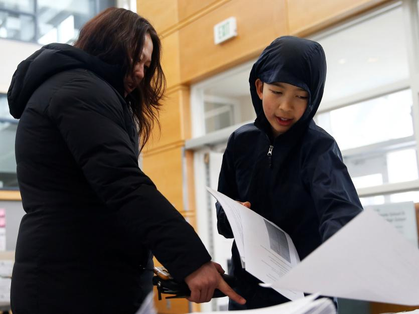 A 6th grader picks up schoolwork packets with his mother during the outbreak of coronavirus disease (COVID-19), in Seattle, Washington, U.S. March 17, 2020.