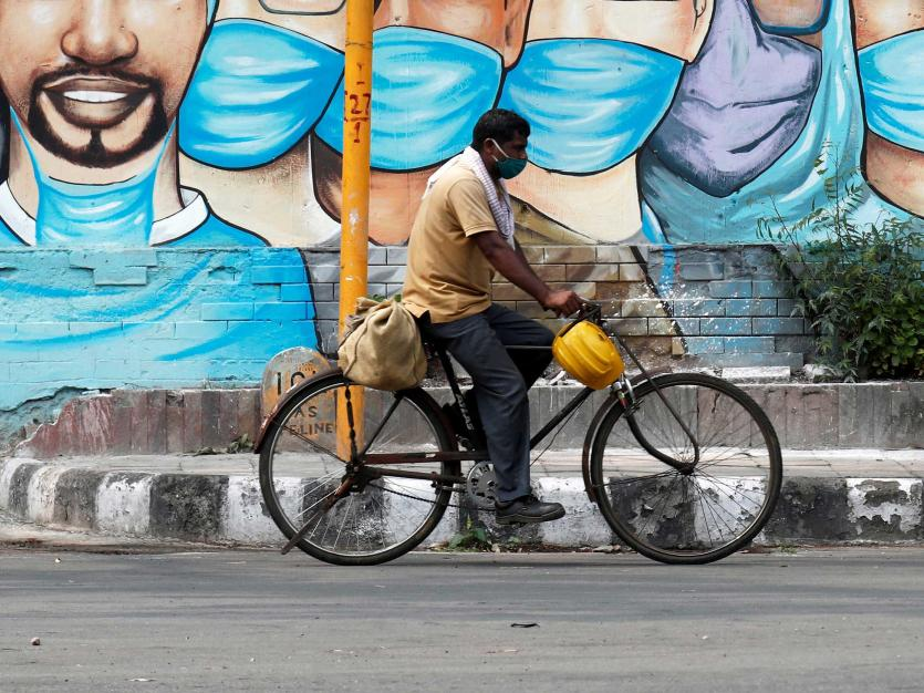 A man rides his bicycle past a graffiti, amidst the spread of the coronavirus disease (COVID-19), in New Delhi, India, July 17, 2020.