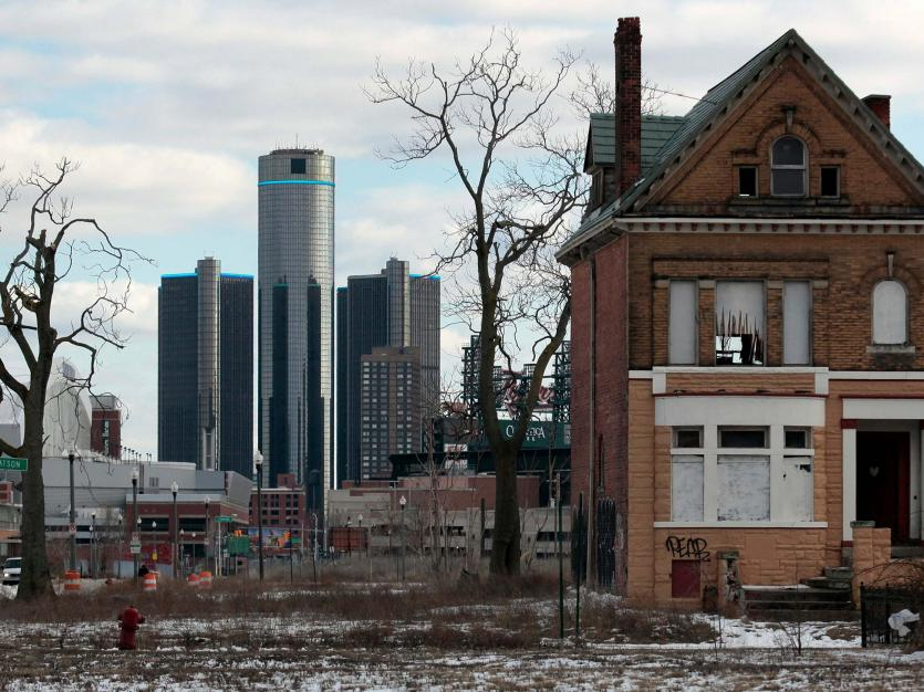 A vacant, boarded up house is seen in the once thriving Brush Park neighborhood with the downtown Detroit skyline behind it in Detroit, Michigan March 3, 2013