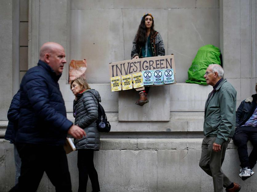 A protester holds a banner during a demonstration at the Bank of England in the City of London, Britain October 14, 2019.