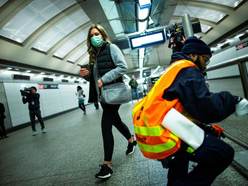 A woman wearing a face mask walks past an MTA worker disinfecting a subway station in the Manhattan borough of New York City, New York, U.S., March 4, 2020. REUTERS/Eduardo Munoz