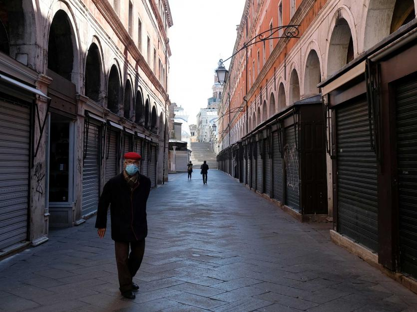 A man wearing a protective mask in an empty street of Venice on Sunday with an unprecedented lockdown across of all Italy imposed to slow the outbreak of coronavirus, in Venice, Italy, March 15, 2020.