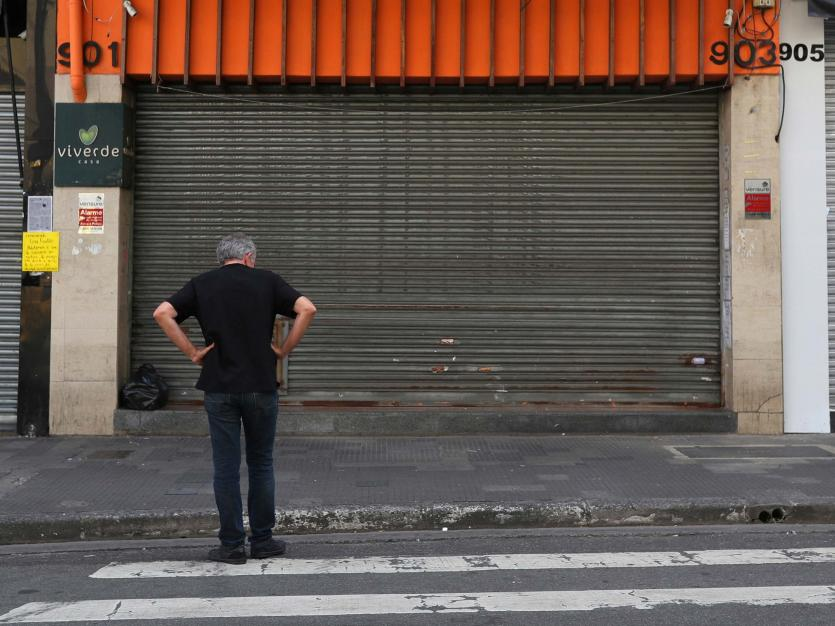 A man is seen in front of closed stores after the closure of shops and stores as a precautionary measure against coronavirus disease (COVID-19) in South America, March 20, 2020.