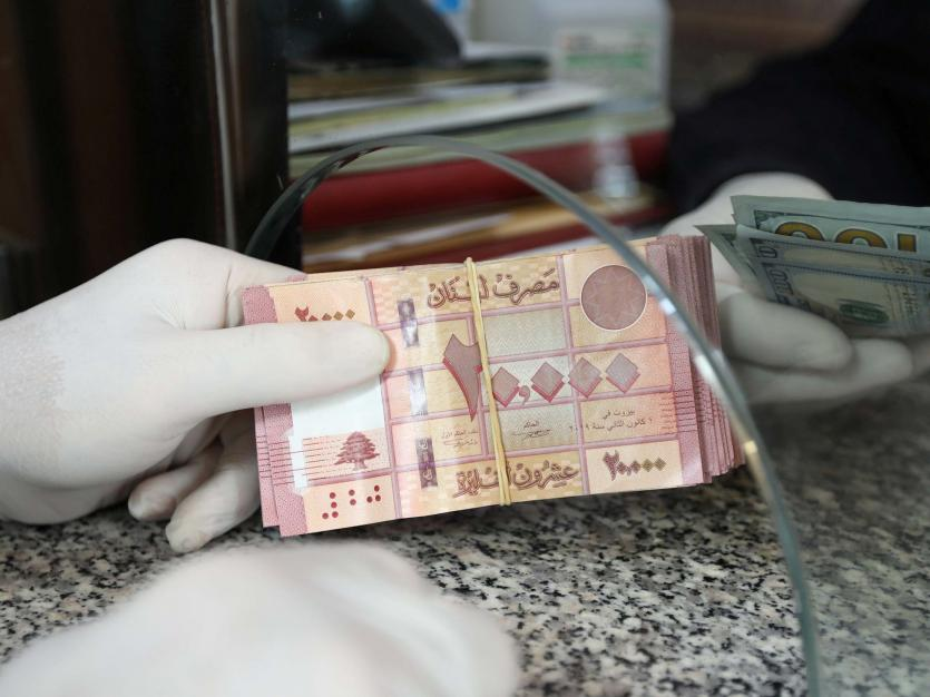 A customer wearing gloves holds Lebanese pounds at a currency exchange store, during a countrywide lockdown to combat the spread of coronavirus disease (COVID-19) in Beirut, Lebanon April 3, 2020.