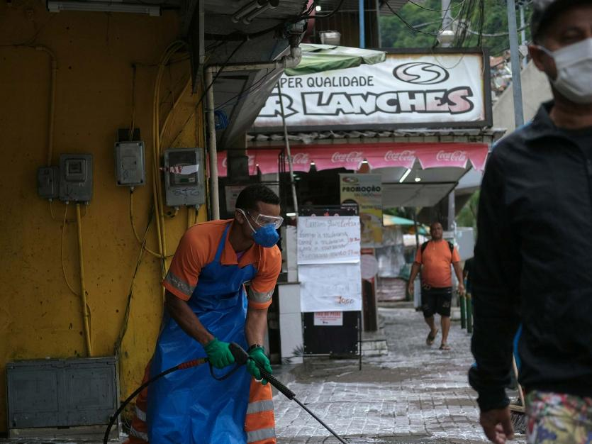 Cleaners disinfect the streets of Rocinha slum during the coronavirus disease (COVID-19) outbreak, in Rio de Janeiro, Brazil April 10, 2020.