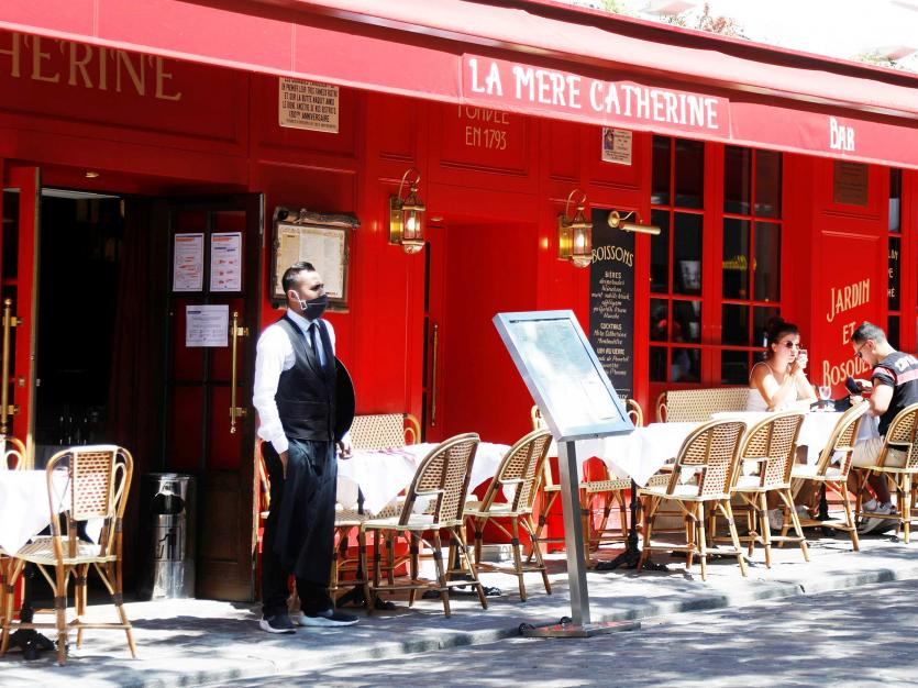 A waiter wearing a face mask waits for customers at La Mere Catherine, Place du Tertre at Montmartre in Paris as restaurants and cafes reopen following the coronavirus disease (COVID-19) outbreak in. France, June 2, 2020