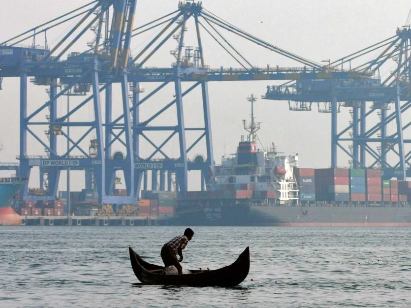 A fisherman prepares to cast his fishing net in the waters of the Vembanad lake as a container ship is seen docked in the background, at a port in Vallarpadam, in the southern Indian city of Kochi, February 2014