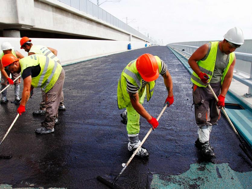 Workers pave a road on a newly constructed bridge southwest of Bucharest, May 8, 2013. The bridge construction project is one of the most important projects supported by the European Union.