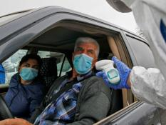 A medical official wearing protective gear takes the body temperature of a driver and a passenger, as an additional measure to prevent the spread of coronavirus disease (COVID-19), at a check point outside Bishkek, Kyrgyzstan March 23, 2020.