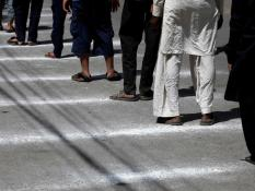 People stand on marked lines to maintain safe distance, as the buy a low-priced food from a charity stall, during a lockdown after Pakistan shut all markets, public places and discouraged large gatherings amid an outbreak of coronavirus disease (COVID-19)