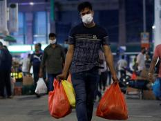 A man wearing a protective mask carries bags of groceries, before tighter measures are implemented to curb the coronavirus disease (COVID-19) outbreak, in Singapore, April 5, 2020.