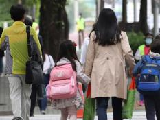 Elementary students walk to school with their mother in Seoul, South Korea on June 2, 2020.