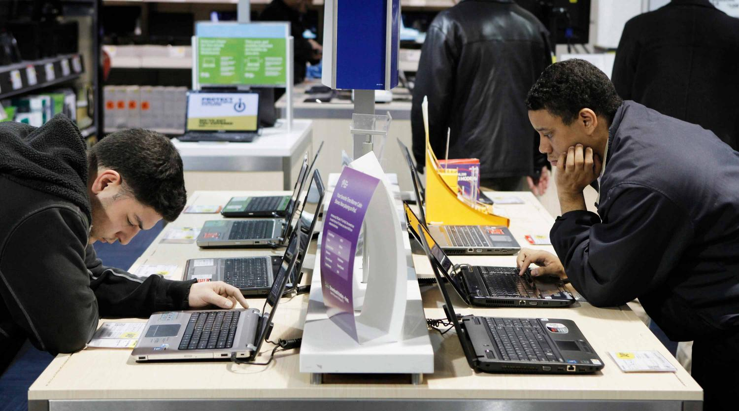 Two men inspect laptop computers while shopping in a Best Buy store in New York City.