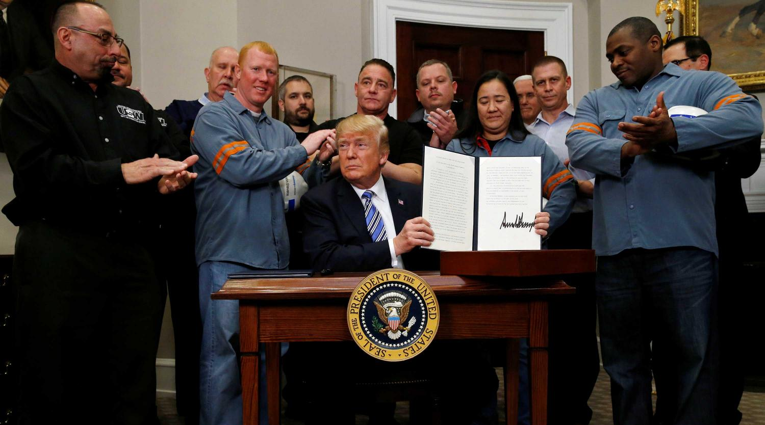 U.S. President Donald Trump poses as he signs a presidential proclamation placing tariffs on steel and aluminum imports while surrounded by workers from the steel and aluminum industries at the White House in Washington, U.S. March 8, 2018.