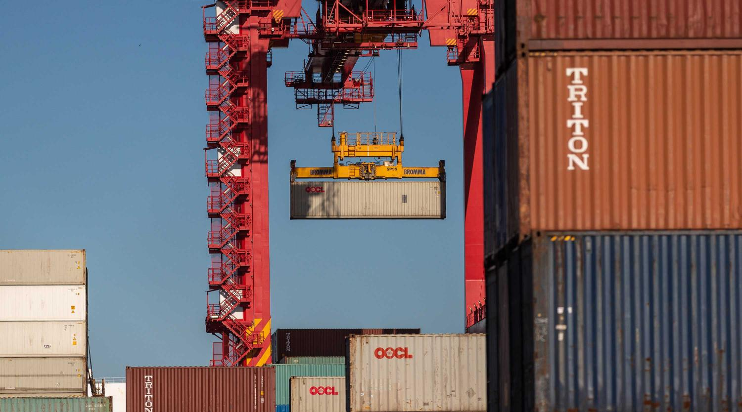 Shipping containers are seen being moved, Monday, August 16, 2021.