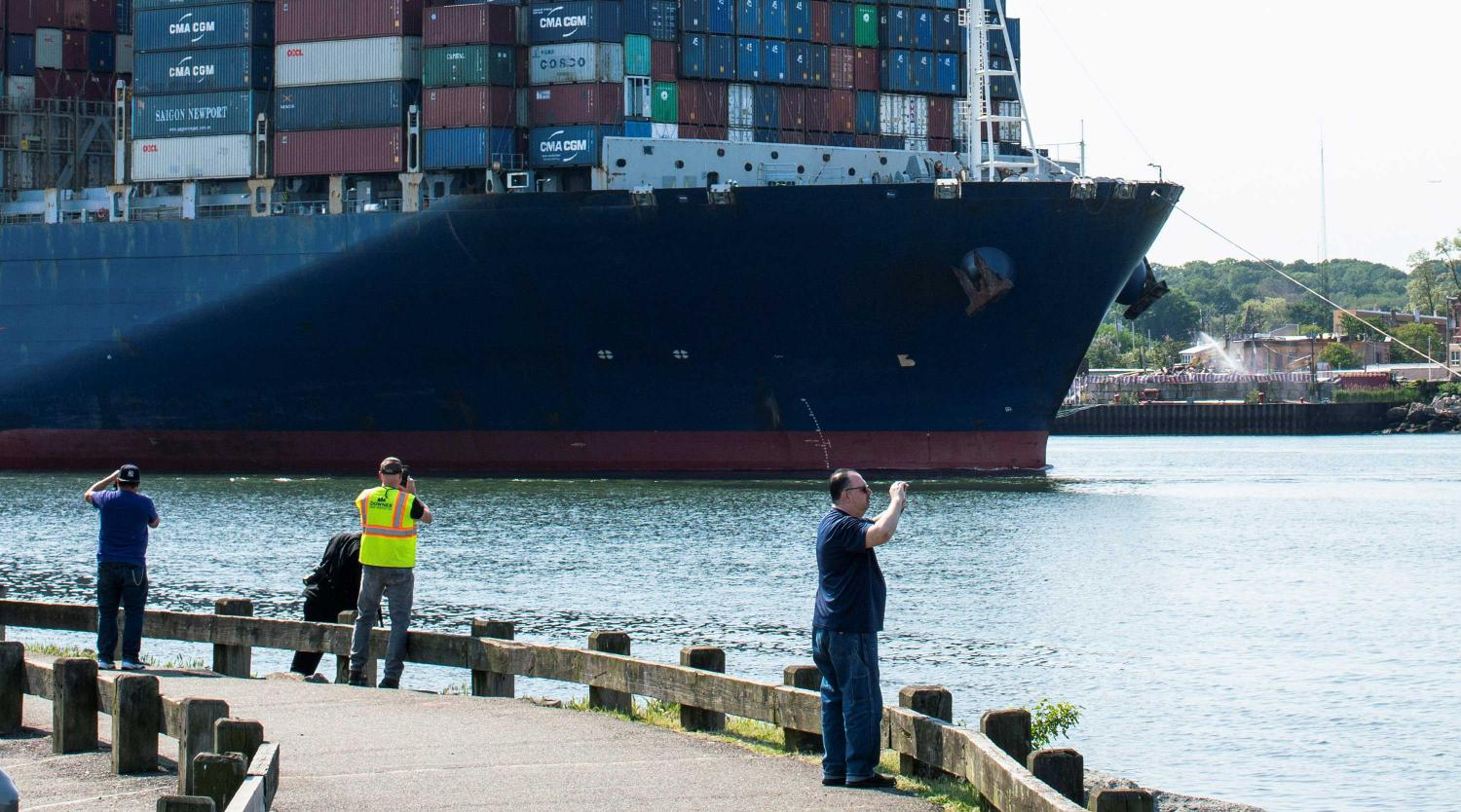 :  People take a look at a container ship entering Newark bay to dock in Elizabeth port as seen from Bayonne, New Jersey, U.S., May 20, 2021
